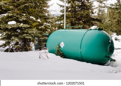 Green Propane Tank in a Snowy Yard with Pine Trees in Banckground