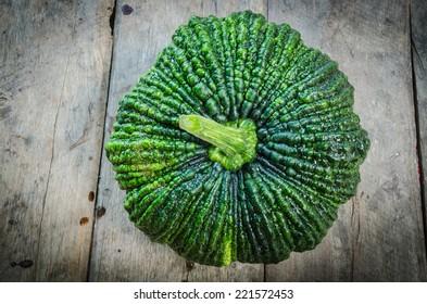 Green pumpkin on a wooden floor