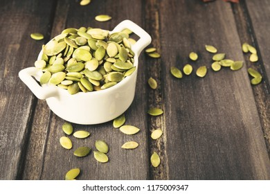 Green pumpkin seeds in white bowl on grey wooden background with copy space, toned photo