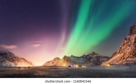 Green and purple aurora borealis over snowy mountains. Northern lights in Lofoten islands, Norway. Starry sky with polar lights. Night winter landscape with aurora, high rocks, beach. Travel. Nature