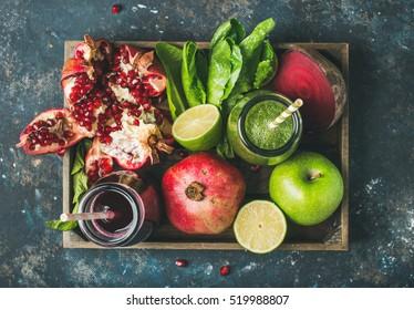 Jus de fruits frais verts et violets ou smoothies avec fruits, verts, légumes dans un plateau en bois, vue de dessus, mise au point sélective. Détoxe, régime, alimentation propre, végétalien, végétalien, fitness, mode de vie sain