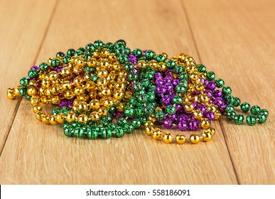 Green, purple, and gold mardi gras beads isolated on wood