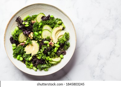 Green and purple kale salad with beans, avocado and cucumber. Healthy vegan food concept.