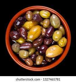 green and purple, mixed olives in clay bowl - isolated on black background