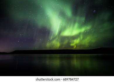 Green and purple northern lights over Kleifarvatn lake on the Reykjanes Peninsula of Iceland with bright groups of stars in the night sky and reflection in the lake water