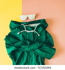 green raincoat and white sunglasses on pink and yellow background. minimal flat lay