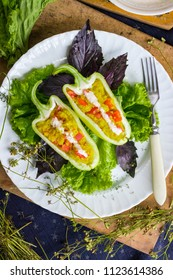 Green raw bell peppers stuffed with quinoa, bulgur, tomato, basil leaves and other vegetables with oil and rock salt for lunch or dinner. Vegan vegetarian healthy food.