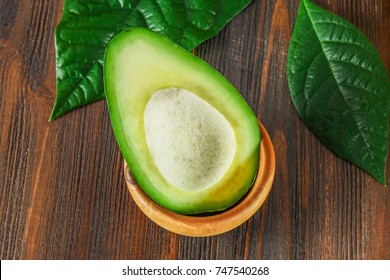 A green, raw, ripe, avocado-cut fruit without seeds lies in a wooden bowl, surrounded by leaves on a brown table