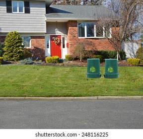 Green recycle, reuse, reduce, trash container suburban brick high ranch home sunny residential neighborhood USA