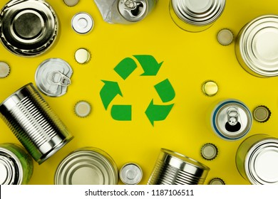 Green recycle reuse sign symbol with metal aluminium cans, covers, jars on yellow background. Eco ecology environment garbage recycling concept