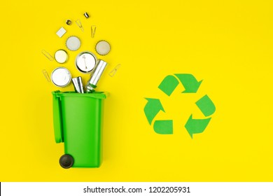 Green recycle reuse sign symbol with metal aluminum trash garbage with green trash bin on yellow background. Eco ecology environment issue care garbage recycling reuse, safe planet, ecology concept