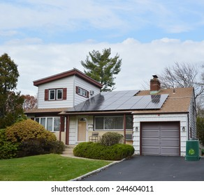 Green recycle trash container Suburban Ranch style home with solar panel on roof residential neighborhood USA blue sky clouds