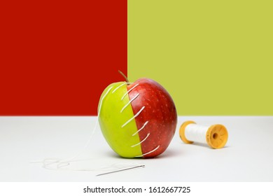 Green and red apple stitched together with a needle and tread