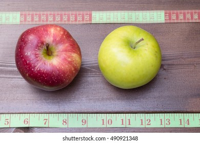 Green and red apples with measuring tape on the wooden table. Diet concept