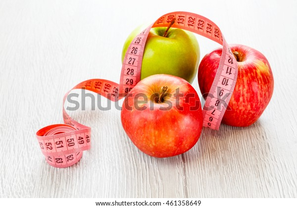 Green and red apples with meter on a wooden background