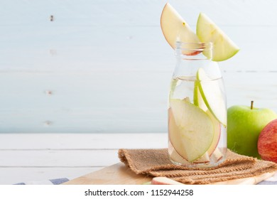 Green and red apples in soda bottle on white table
