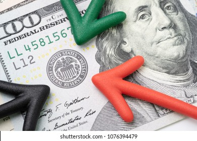 Green, red and black arrow pointing to US Federal Reserve emblem on hundred dollars banknote as FED consider interest rate hike, economics and inflation control national organization.