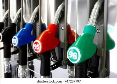 Green red blue black fuel pistols on fuel station.