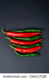 Green and red chili peppers on black background, top view. Hot spicy food symbol.