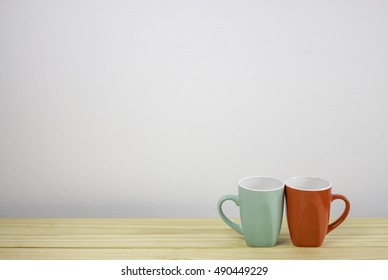 green and red coffee mug on wooden table. focus on mug
