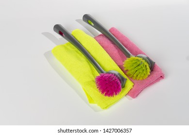 Green and red dishwashing brushes with cloths in the same colours.