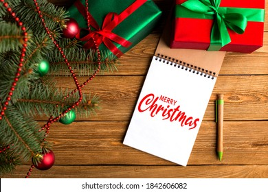 Green red gifts and notepad under the tree, on the table, against the wood background. The concept of Christmas and New Year.