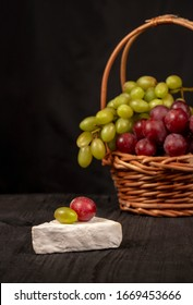 green and red grapes in a basket with brie cheese on a rustic wooden table, still life
