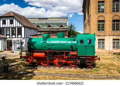 Green and red locomotive on tracks at a train station