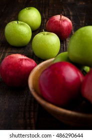 Green and red organic  apples in bowl on wooden board. Healthy food