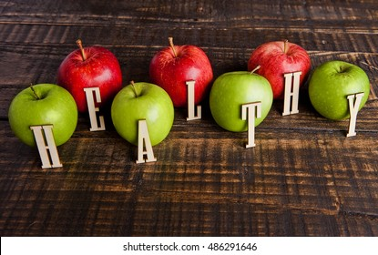 Green and red organic healthy apples on wooden board. With letters