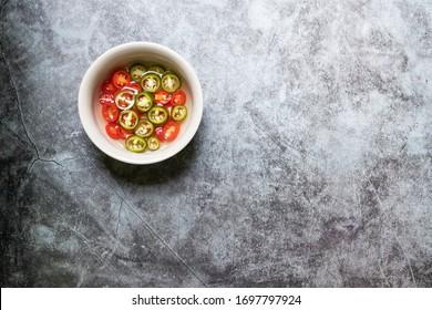 Grüne und rote pickierte Chilischoten in Essig mit Kopienraum auf dem Hintergrund. Draufsicht