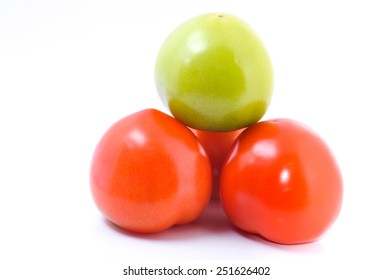 Green and red tomato on white background