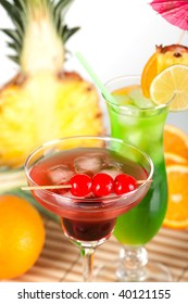 Green and red tropical cocktails with pineapple and cherry