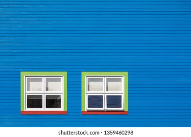 Green, red and white windows on a blue wooden wall. Minimalism style of the houses of Iles de la Magdalen, Canada, in bright colours with space for text.