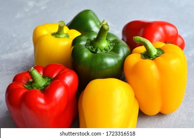 Green, red and yellow bell pepper on grey stone background. Organic healthy food