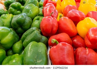 Green, red, and yellow peppers for sale in a market. The peppers are wet with water spray. Closeup view.