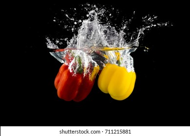 Green, red, and yellow sweet pepper drop and splash in water with black background.