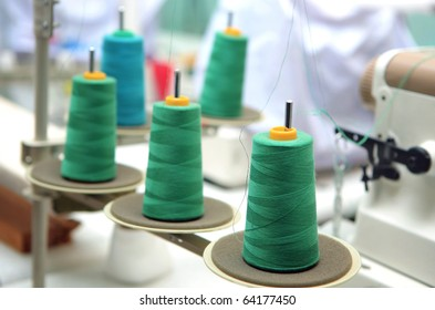 green reels of textile yarn thread at manufacturing machine.