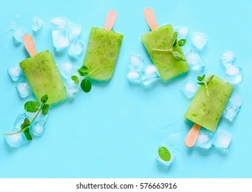Green refreshing mint popsicles with ice cubes decorated with mint leaves, view from above