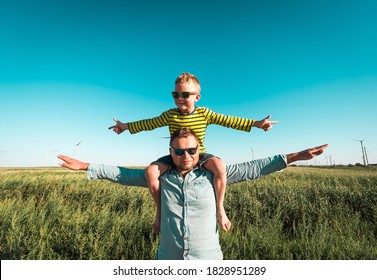 Green renewable energy concept. Happy family playing on field with wind generator turbines. Father carrying little kid boy on shoulders and waving their arms like a windmill.