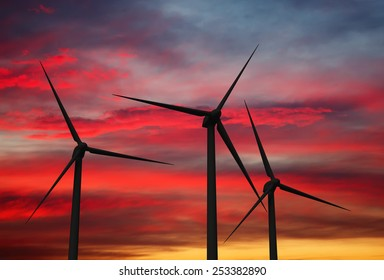 Green renewable energy concept - wind generator turbines in sky on sunset