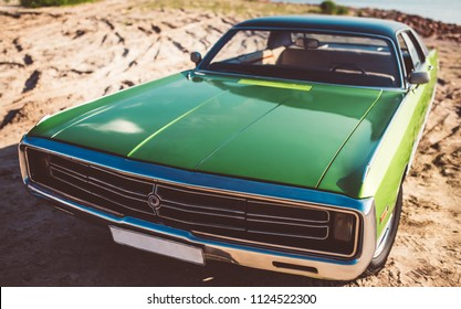 Green retro car is standing on the beach. Vintage classic car. Old and stylish. Muscle car.