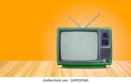green retro old television receiver on table front gradient orange  wall background,perspective wooden floor texture and,vintage tv