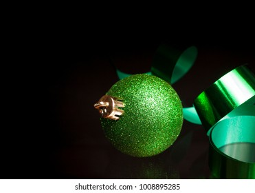Green ribbon and a Christmas ornament on a black background