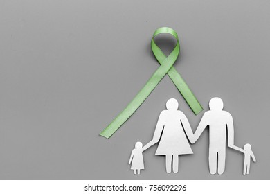Green ribbon for Lyme disease, kidney cancer, organ donation awareness near paper silhouette of family on dark wooden background top view