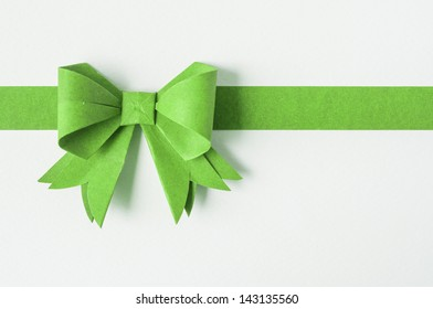 Green ribbon on white recycled paper. Paper craft .