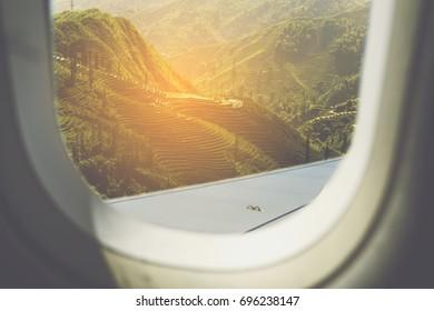 Green Rice fields on terraced as seen through window of an aircraft.