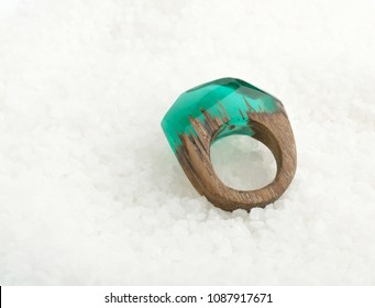 Green Ring Made of Wood and Resin. Handmade Bijouterie on White Crystal Background