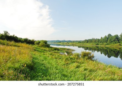 green riverside of small river in summer day, Russia
