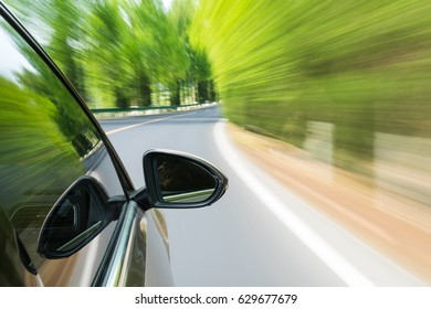 green road with car driving motion blur